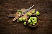 Fresh raw Brussels sprouts on a wooden background.