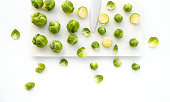 Brussels sprouts and knife on marble chopping board and white background.