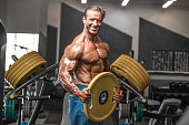 Brutal strong bodybuilder athletic aged man pumping up muscles workout bodybuilding concept background - muscular bodybuilder handsome men doing exercises in gym naked torso sport and diet concept