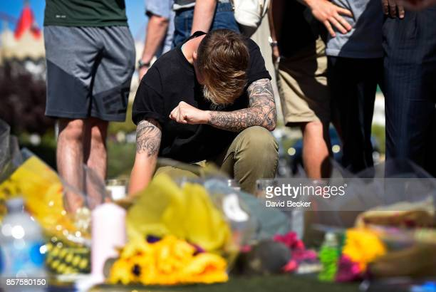 Bry Thompson of Las Vegas kneels at a makeshift memorial set up across from the Las Vegas Village on October 4 2017 in Las Vegas Nevada Thompson had...