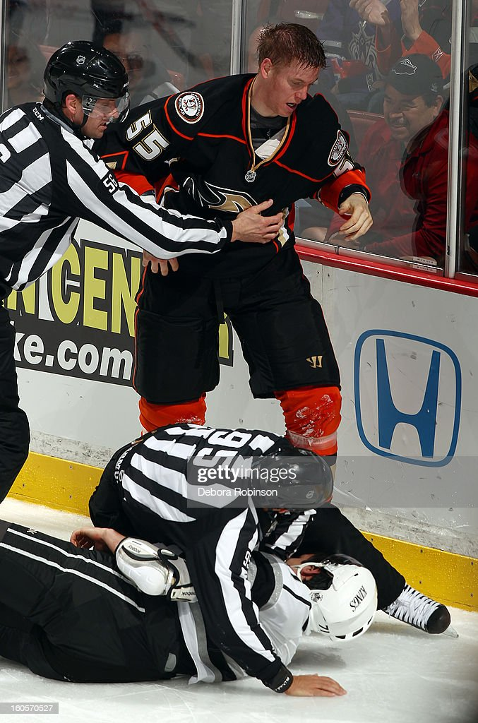 Bryan Allen #55 of the Anaheim Ducks is held back by linesmen Mark Wheler as linesmen Jonny Murray covers up Jordan Nolan #71 of the Los Angeles Kings on February 2, 2013 at Honda Center in Anaheim, California.
