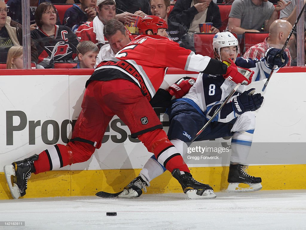 Bryan Allen #5 of the Carolina Hurricanes checks <a gi-track='captionPersonalityLinkClicked' href=/galleries/search?phrase=Alexander+Burmistrov&family=editorial&specificpeople=4782297 ng-click='$event.stopPropagation()'>Alexander Burmistrov</a> #8 of the Winnipeg Jets into the boards during an NHL game on March 30, 2012 at PNC Arena in Raleigh, North Carolina.