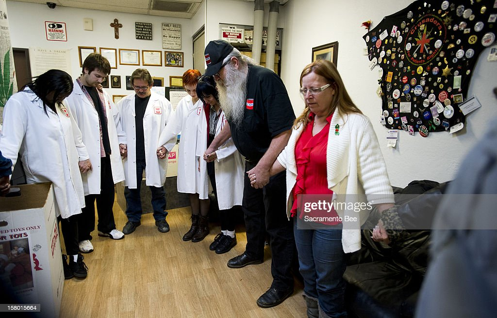 Bryan and Lanette Davies, right, join hands to lead a prayer each day at 6 p.m. for their staff and patients at the Canna Care marijuana dispensary in Sacramento, California.