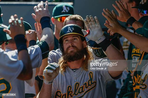 Bryan Anderson of the Oakland Athletics is congratulated by teammates after hitting an RBI sacrifice fly in the third inning against the Seattle...