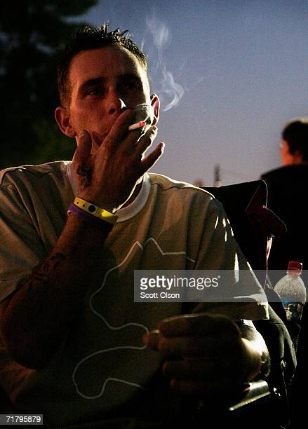 Bryan Anderson smokes a cigarette while chatting with friends at a festival during a break from therapy at Walter Reed Army Medical Center June 30...