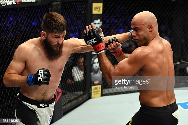 Bryan Barberena punches Warlley Alves of Brazil in their middleweight bout during the UFC 198 event at Arena da Baixada stadium on May 14 2016 in...