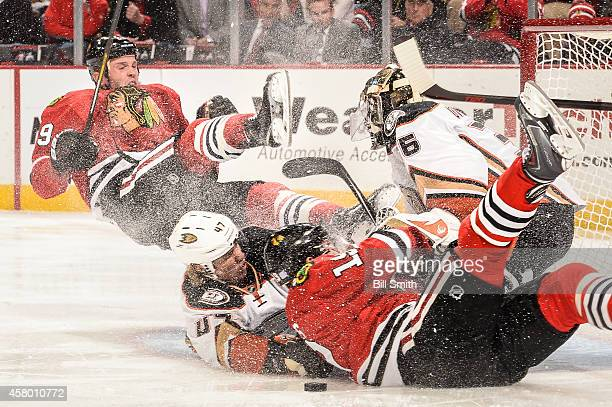 Bryan Bickell and Jonathan Toews Chicago Blackhawks collide with Hampus Lindholm of the Anaheim Ducks into goalie John Gibson during the NHL game on...