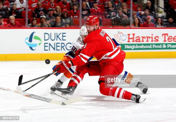 Bryan Bickell of the Carolina Hurricanes and Adam Pelech of the New York Islanders battle for a loose puck in the crease during an NHL game on April...