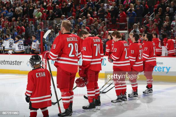 Bryan Bickell of the Carolina Hurricanes and teammates are photographed during the National Anthem prior to an NHL game against the St Louis Blues on...