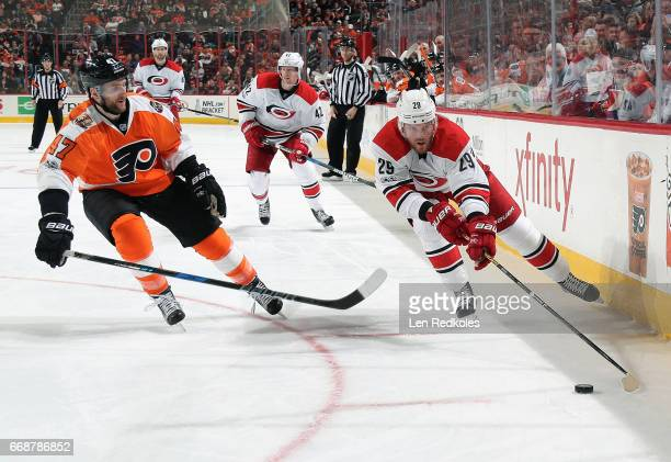 Bryan Bickell of the Carolina Hurricanes skates the puck along the boards against Andrew MacDonald of the Philadelphia Flyers on April 9 2017 at the...