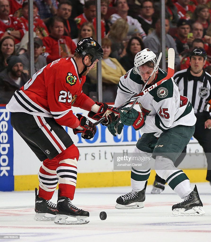 Bryan Bickell #29 of the Chicago Blackhawks and Jonas Brodin #25 of the Minnesota Wild battle for the puck in Game Five of the Second Round of the 2014 NHL Stanley Cup Playoffs at the United Center on May 11, 2014 in Chicago, Illinois. The Blackhawks defeated the Wild 2-1.