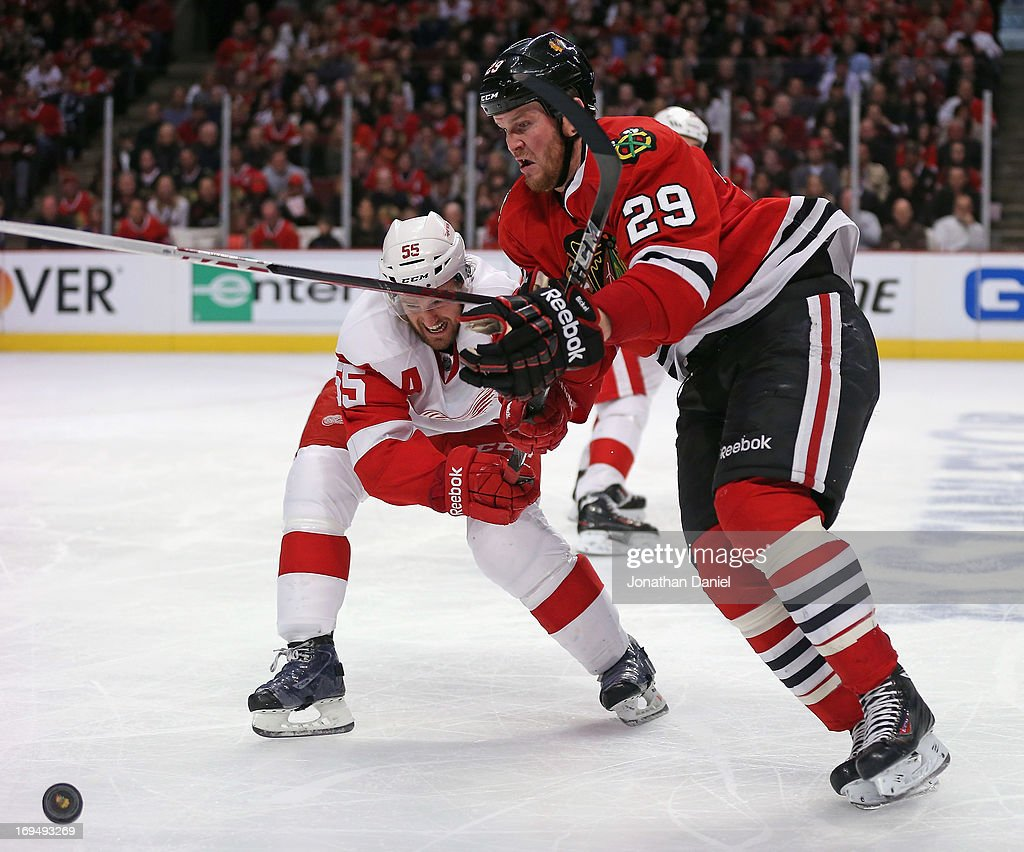Bryan Bickell of the Chicago Blackhawks and Niklas Kronwall of the Detroit Red Wings battle for the puck in Game Five of the Western Conference...