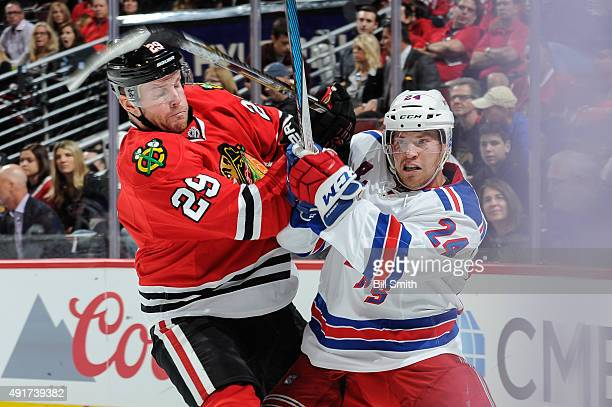 Bryan Bickell of the Chicago Blackhawks and Oscar Lindberg of the New York Rangers get physical during the season opener during an NHL game at the...