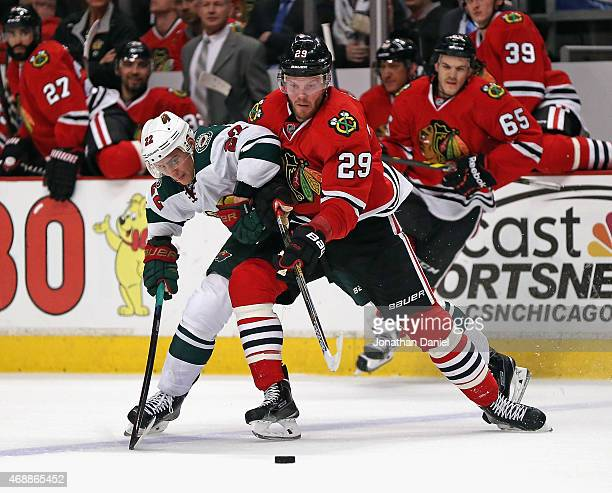 Bryan Bickell of the Chicago Blackhawks battle for the puck with Nino Niederreiter of the Minnesota Wild at the United Center on April 7 2015 in...