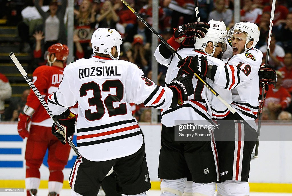 <a gi-track='captionPersonalityLinkClicked' href=/galleries/search?phrase=Bryan+Bickell&family=editorial&specificpeople=241498 ng-click='$event.stopPropagation()'>Bryan Bickell</a> #29 of the Chicago Blackhawks celebrates his third period goal with <a gi-track='captionPersonalityLinkClicked' href=/galleries/search?phrase=Jonathan+Toews&family=editorial&specificpeople=537799 ng-click='$event.stopPropagation()'>Jonathan Toews</a> #19 and <a gi-track='captionPersonalityLinkClicked' href=/galleries/search?phrase=Marian+Hossa&family=editorial&specificpeople=202233 ng-click='$event.stopPropagation()'>Marian Hossa</a> #81 and <a gi-track='captionPersonalityLinkClicked' href=/galleries/search?phrase=Michal+Rozsival&family=editorial&specificpeople=216462 ng-click='$event.stopPropagation()'>Michal Rozsival</a> #32 while playing the Detroit Red Wings in Game Six of the Western Conference Semifinals during the 2013 NHL Stanley Cup Playoffs at Joe Louis Arena on May 27, 2013 in Detroit, Michigan. Chicago won the game 4-3 to tie the series 3-3.