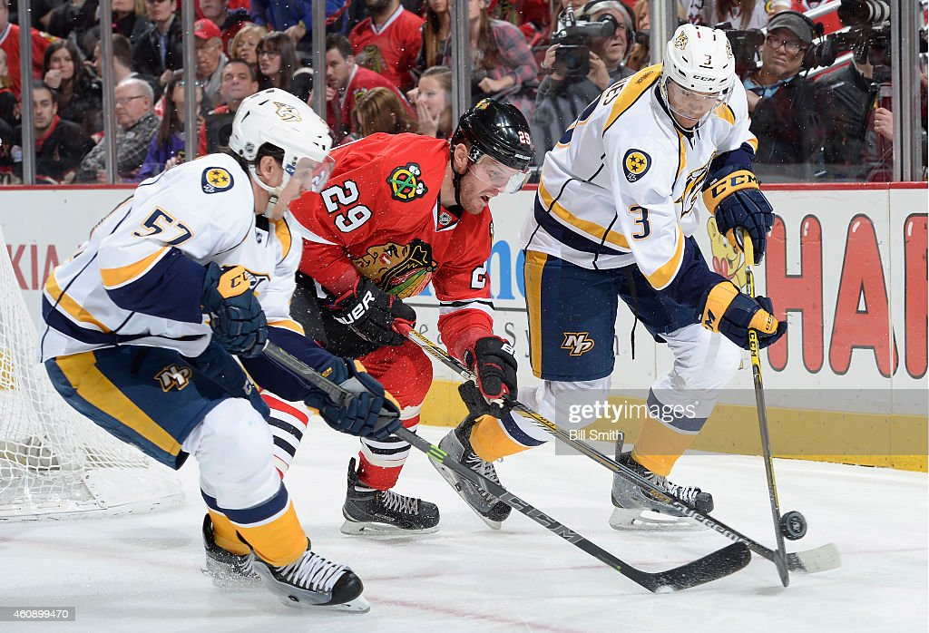 Bryan Bickell #29 of the Chicago Blackhawks chases the puck against Gabriel Bourque #57 and Seth Jones #3 of the Nashville Predators during the NHL game at the United Center on December 29, 2014 in Chicago, Illinois.