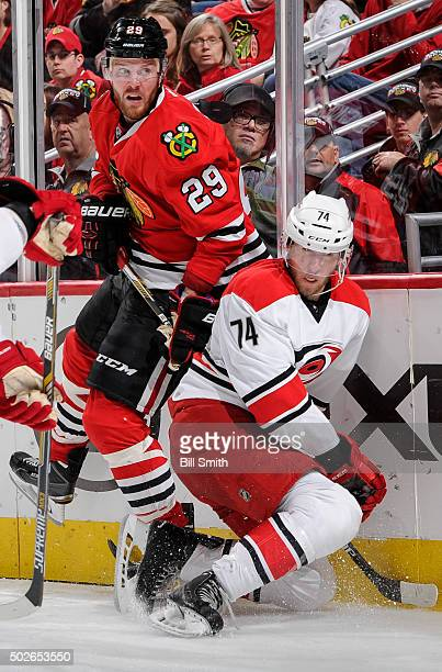 Bryan Bickell of the Chicago Blackhawks checks Jaccob Slavin of the Carolina Hurricanes in the third period of the NHL game at the United Center on...
