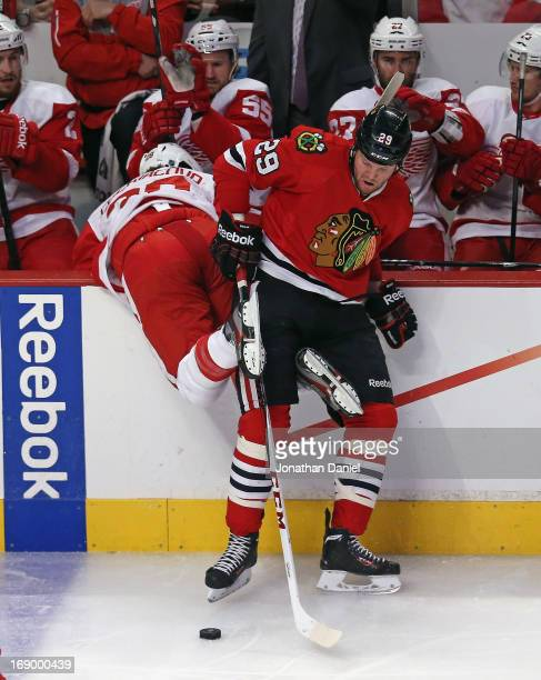 Bryan Bickell of the Chicago Blackhawks dumps Carlo Colaiacovo of the Detroit Red Wings over the boards in Game Two of the Western Conference...