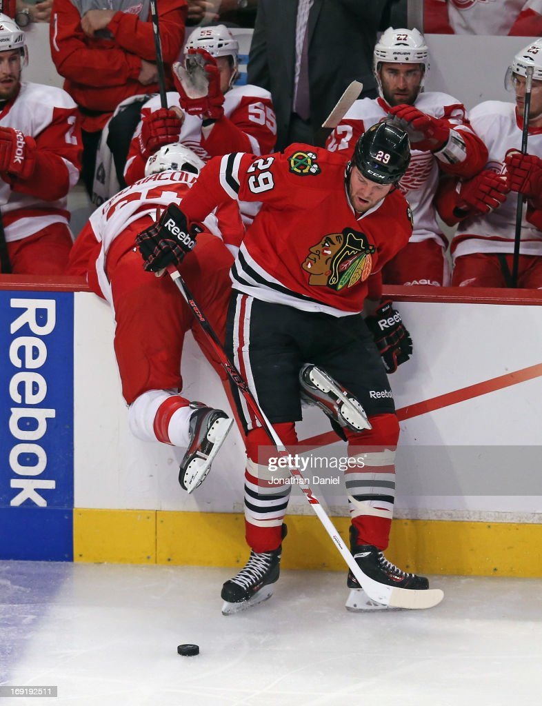 <a gi-track='captionPersonalityLinkClicked' href=/galleries/search?phrase=Bryan+Bickell&family=editorial&specificpeople=241498 ng-click='$event.stopPropagation()'>Bryan Bickell</a> #29 of the Chicago Blackhawks dumps <a gi-track='captionPersonalityLinkClicked' href=/galleries/search?phrase=Carlo+Colaiacovo&family=editorial&specificpeople=234960 ng-click='$event.stopPropagation()'>Carlo Colaiacovo</a> #28 of the Detroit Red Wings over the boards in Game Two of the Western Conference Semifinals during the 2013 NHL Stanley Cup Playoffs at the United Center on May 18, 2013 in Chicago, Illinois. The Red Wings defeated the Blackhawks 4-1.