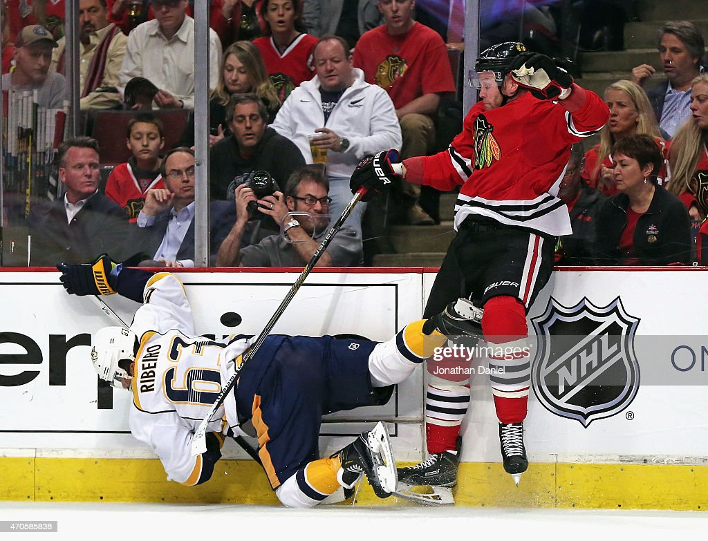 Bryan Bickell of the Chicago Blackhawks dumps Mike Ribeiro of the Nashville Predators in Game Four of the Western Conference Quarterfinals during the...