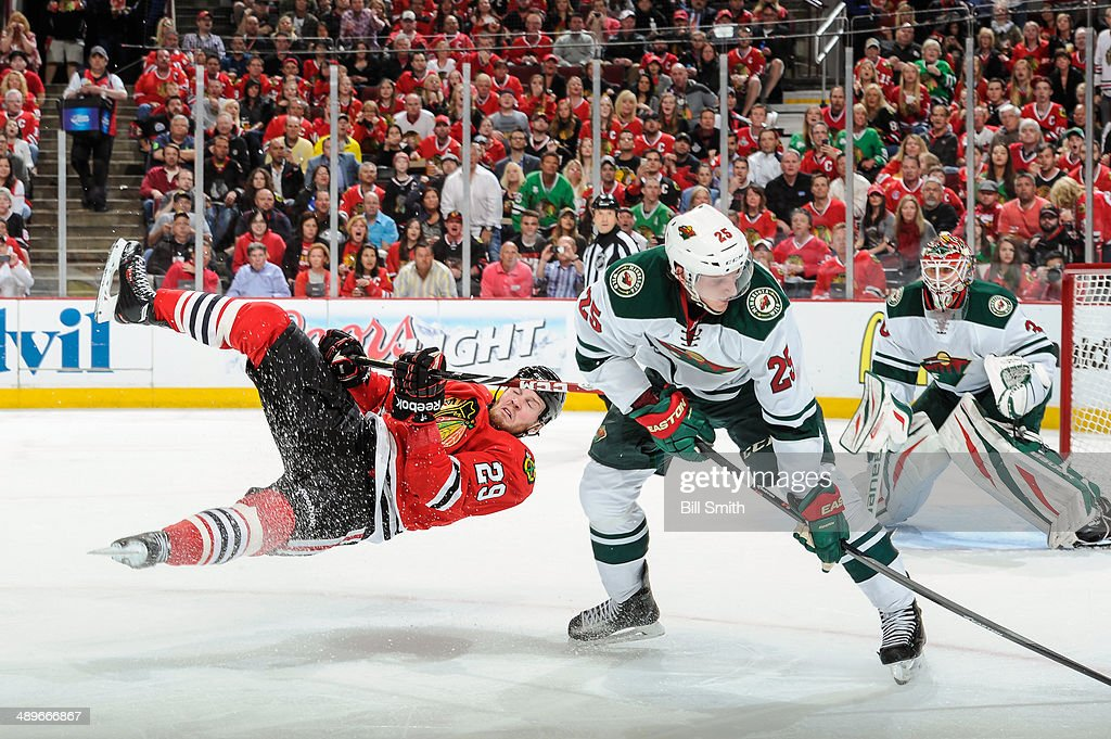Bryan Bickell #29 of the Chicago Blackhawks flies through the air as Jonas Brodin #25 of the Minnesota Wild watches for the puck in Game Five of the Second Round of the 2014 Stanley Cup Playoffs at the United Center on May 11, 2014 in Chicago, Illinois.