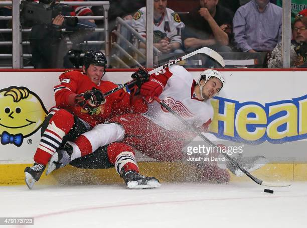 Bryan Bickell of the Chicago Blackhawks is called for a hooking penalty after taking down Jonathan Ericsson of the Detroit Red Wings at the United...
