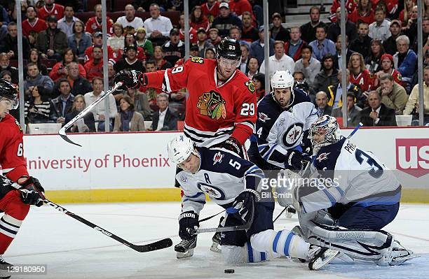 Bryan Bickell of the Chicago Blackhawks pushes into Mark Stuart of the Winnipeg Jets as Michael Frolik of the Blackhawks rushes in from the side to...