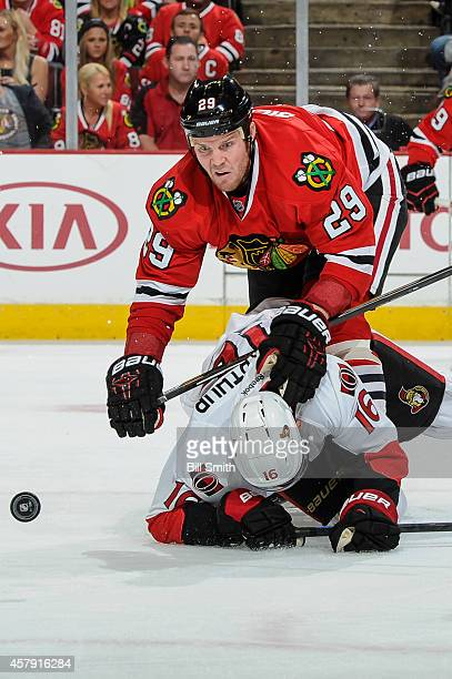 Bryan Bickell of the Chicago Blackhawks stumbles over Clarke MacArthur of the Ottawa Senators while chasing the puck during the NHL game on October...