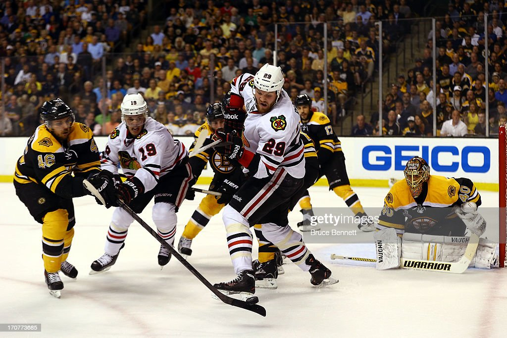 Bryan Bickell #29 of the Chicago Blackhawks tries to handle the puck against David Krejci #46 of the Boston Bruins in Game Three of the 2013 NHL Stanley Cup Final at TD Garden on June 17, 2013 in Boston, Massachusetts.