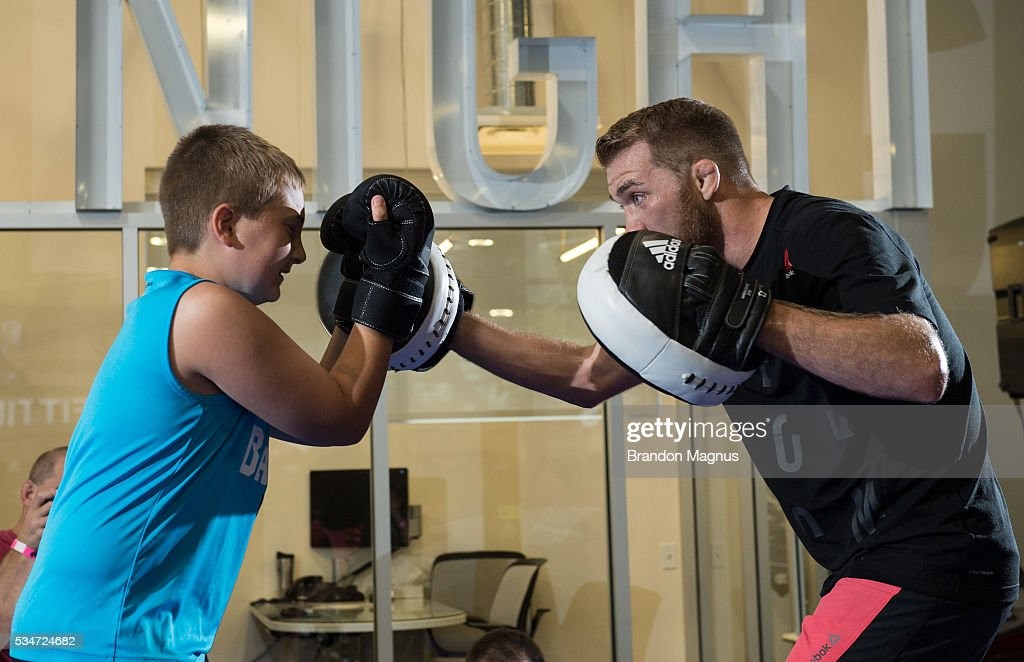 Bryan Caraway brings a fan on stage after holding an open workout for the fans and media at the Las Vegas Harley-Davidson on May 27, 2016 in Las Vegas Nevada.