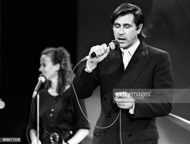 Bryan Ferry of Roxy Music performs with Patty Zomer from Dutch girlband Dolly Dots as a stand in while rehearsing for the TV show 'Footballer Of The...