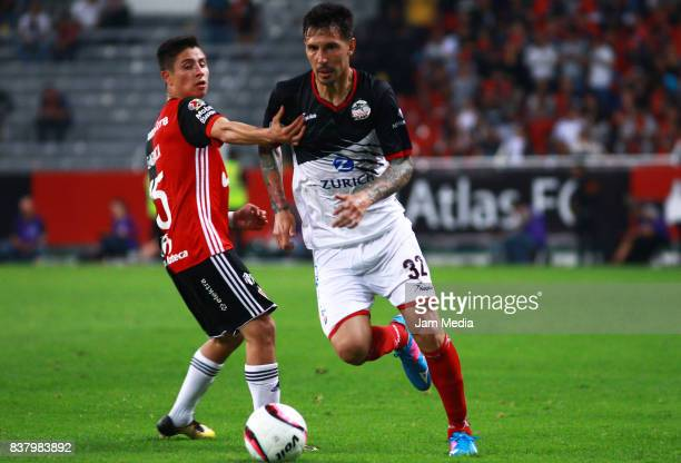 Bryan Garnica of Atlas and Jonathan Fabbro of Lobos BUAP fight for the ball during the 6th round match between Atlas and Lobos BUAP as part of the...