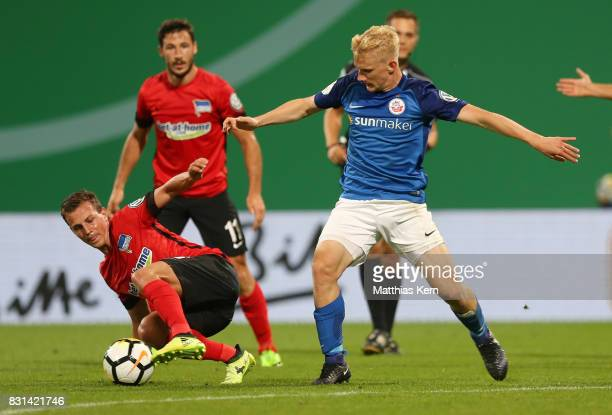 Bryan Henning of Rostock battles for the ball with Vladimir Darida of Berlin during the DFB Cup first round match between FC Hansa Rostock and Hertha...