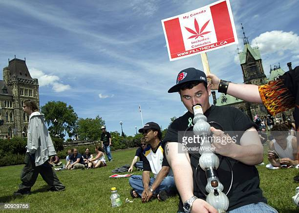 Bryan James of Waterdown Ontario smokes a bong during a rally in support of legalizing marijuana on June 5 2004 on Parliament Hill in Ottawa Canada...