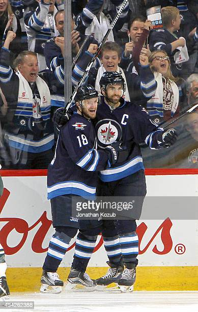 Bryan Little and Andrew Ladd of the Winnipeg Jets celebrate a first period goal against the Minnesota Wild at the MTS Centre on October 25 2015 in...