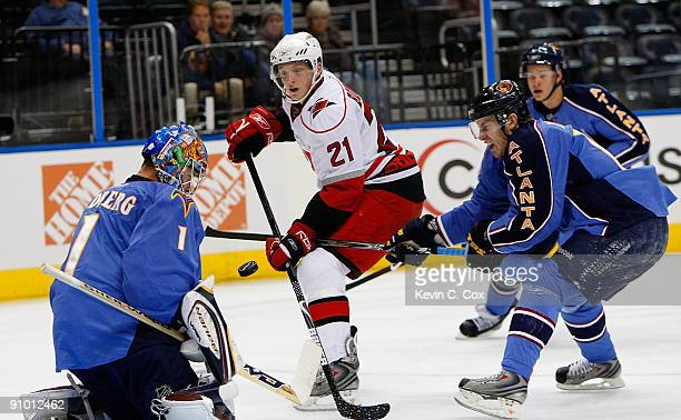 Bryan Little defends as goaltender Johan Hedberg of the Atlanta Thrashers saves a shot on goal by Drayson Bowman of the Carolina Hurricanes during a...