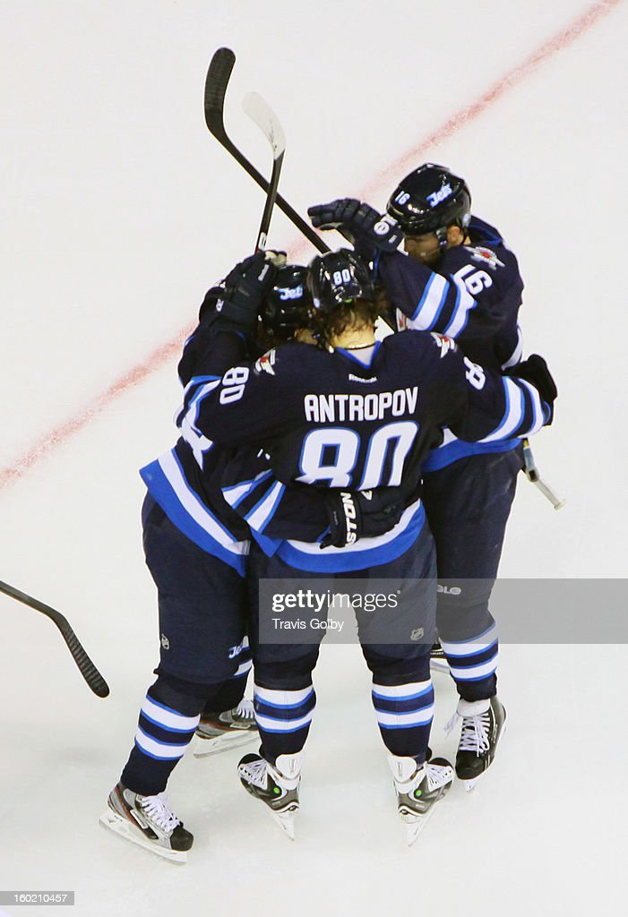 Bryan Little #18, Nik Antropov #80 and Andrew Ladd #16 of the Winnipeg Jets celebrate a second period goal against the New York Islanders at the MTS Centre on January 27, 2013 in Winnipeg, Manitoba, Canada.