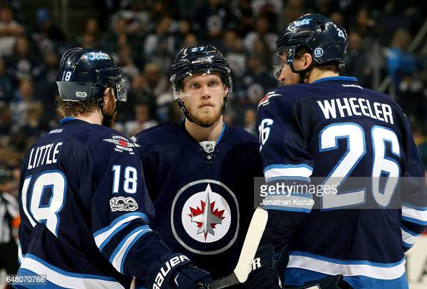 Bryan Little Nikolaj Ehlers and Blake Wheeler of the Winnipeg Jets discuss strategy during a second period stoppage in play against the Colorado...