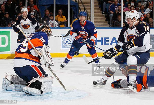 Bryan Little of the Atlanta Thrashers swats at the puck as Goaltender Al Montoya of the New York Islanders gets into position to make the save on...