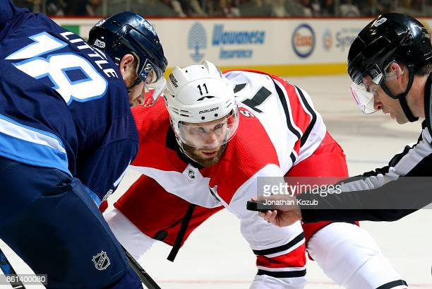 Bryan Little of the Winnipeg Jets and Jordan Staal of the Carolina Hurricanes eye the puck as they await puck drop during first period action at the...