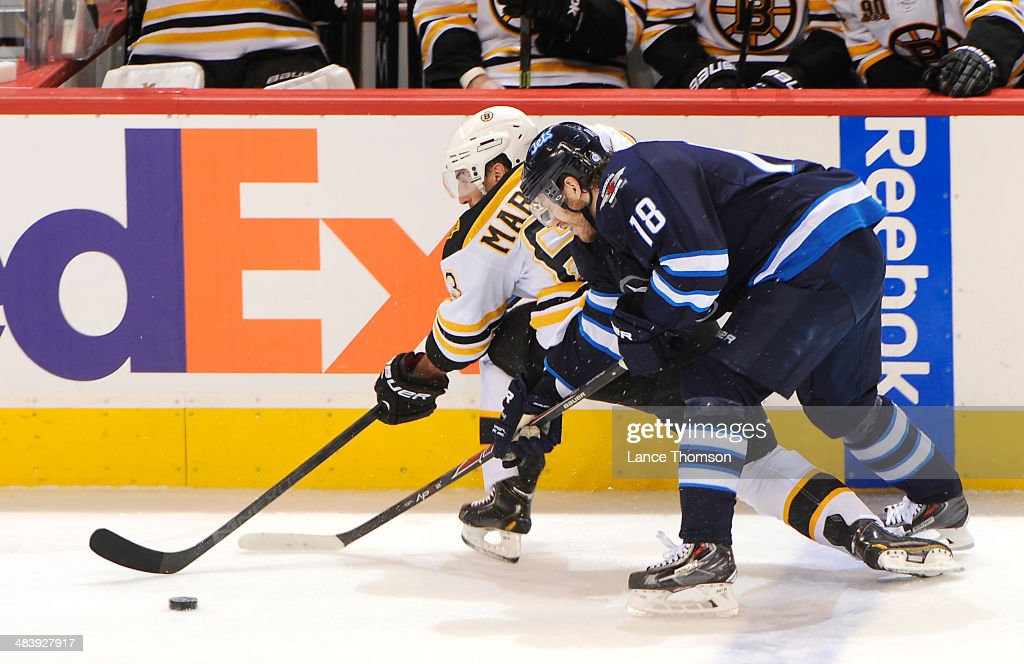 Bryan Little #18 of the Winnipeg Jets battles Brad Marchand #63 of the Boston Bruins as they chase the loose puck during second period action at the MTS Centre on April 10, 2014 in Winnipeg, Manitoba, Canada.