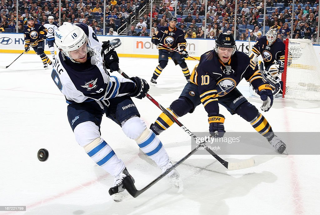 Bryan Little #18 of the Winnipeg Jets battles for the puck against Christian Ehrhoff #10 of the Buffalo Sabres at First Niagara Center on April 22, 2013 in Buffalo, New York.