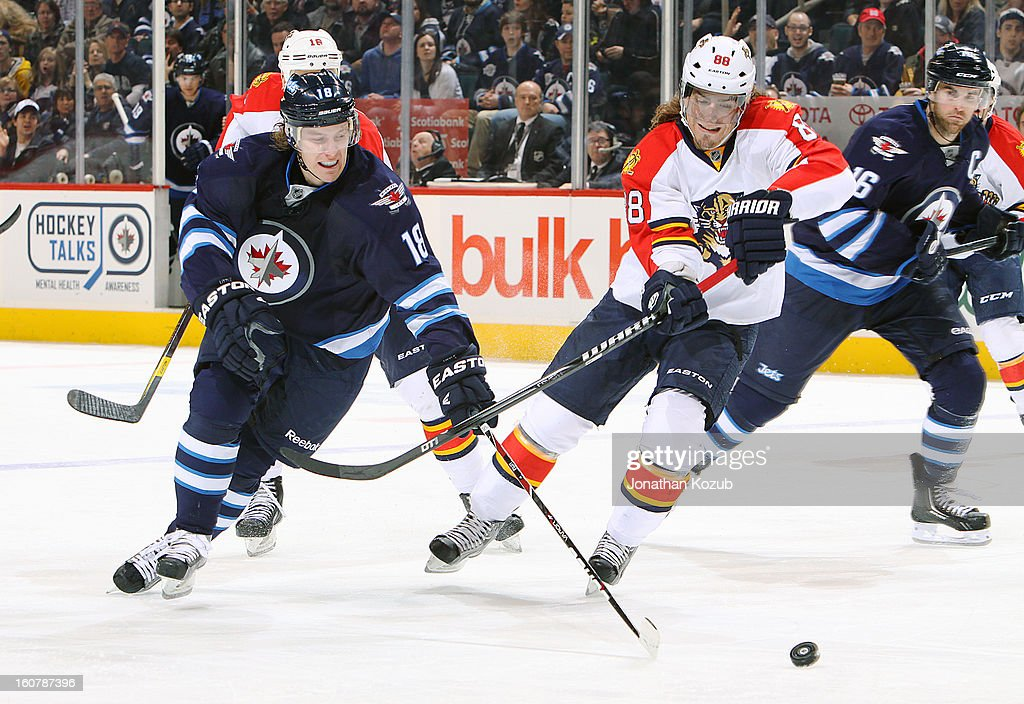Bryan Little #18 of the Winnipeg Jets battles Peter Meuller #88 of the Florida Panthers over a loose puck during third period action at the MTS Centre on February 5, 2013 in Winnipeg, Manitoba, Canada.