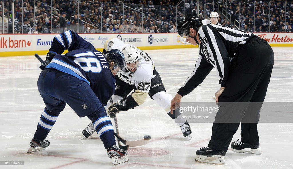 Bryan Little #18 of the Winnipeg Jets battles Sidney Crosby #87 of the Pittsburgh Penguins for the puck during a third period face-off at the MTS Centre on February 15, 2013 in Winnipeg, Manitoba, Canada.