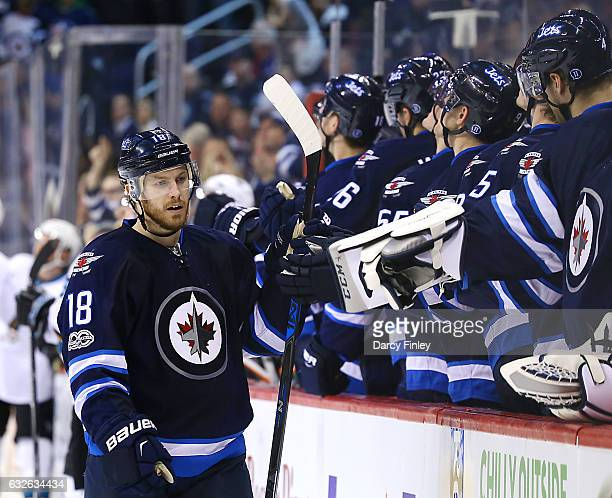 Bryan Little of the Winnipeg Jets celebrates a third period goal against the San Jose Sharks with teammates at the bench at the MTS Centre on January...