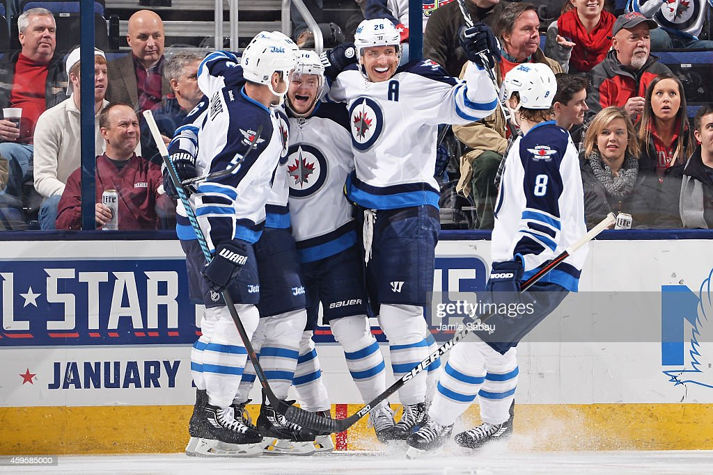<a gi-track='captionPersonalityLinkClicked' href=/galleries/search?phrase=Bryan+Little&family=editorial&specificpeople=540533 ng-click='$event.stopPropagation()'>Bryan Little</a> #18 of the Winnipeg Jets celebrates his first period goal with teammates Mark Stuart #5, <a gi-track='captionPersonalityLinkClicked' href=/galleries/search?phrase=Blake+Wheeler&family=editorial&specificpeople=716703 ng-click='$event.stopPropagation()'>Blake Wheeler</a> #26 and <a gi-track='captionPersonalityLinkClicked' href=/galleries/search?phrase=Jacob+Trouba&family=editorial&specificpeople=8050718 ng-click='$event.stopPropagation()'>Jacob Trouba</a> #8 of the Winnipeg Jets during a game against the Columbus Blue Jackets on November 25, 2014 at Nationwide Arena in Columbus, Ohio.