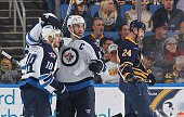 Bryan Little of the Winnipeg Jets celebrates his first period goal against the Buffalo Sabres with teammate Blake Wheeler while Tyson Strachan of the...