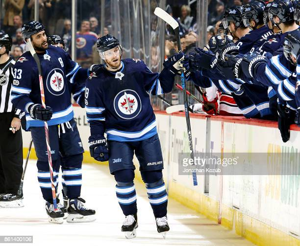 Bryan Little of the Winnipeg Jets celebrates his first period goal against the Carolina Hurricanes with teammates at the bench at the Bell MTS Place...