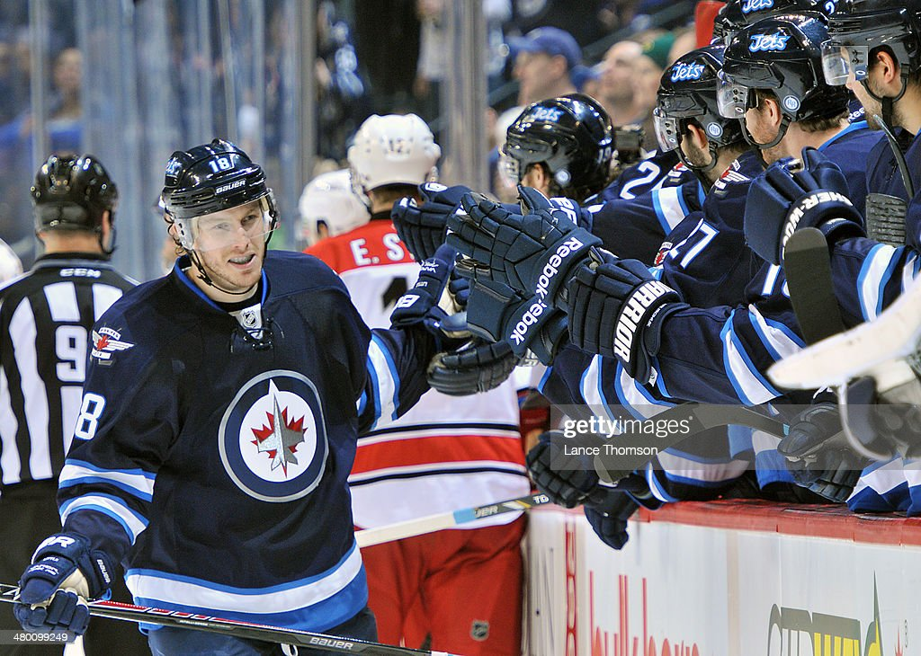 <a gi-track='captionPersonalityLinkClicked' href=/galleries/search?phrase=Bryan+Little&family=editorial&specificpeople=540533 ng-click='$event.stopPropagation()'>Bryan Little</a> #18 of the Winnipeg Jets celebrates his third period goal against the Carolina Hurricanes with teammates at the bench at the MTS Centre on March 22, 2014 in Winnipeg, Manitoba, Canada.