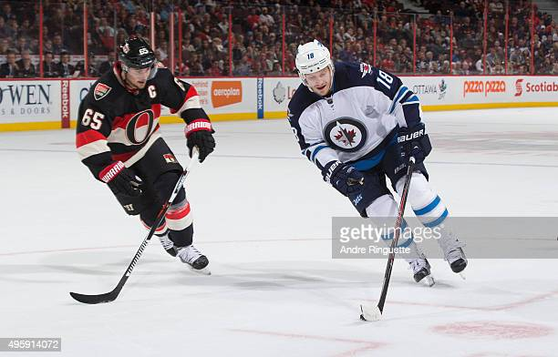 Bryan Little of the Winnipeg Jets controls the puck against Erik Karlsson of the Ottawa Senators at Canadian Tire Centre on November 5 2015 in Ottawa...